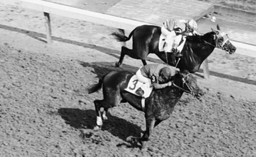 """Ismael """"Milo"""" Valenzuela rides Tim Tam, foreground, to victory before 118,000 spectators during the 1958 Kentucky Derby."""