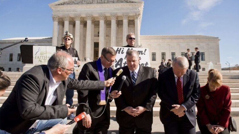 Outside the Supreme Court in 2013, religious activists pray following oral arguments in the case of Town of Greece vs. Galloway, which deals with prayer in government.