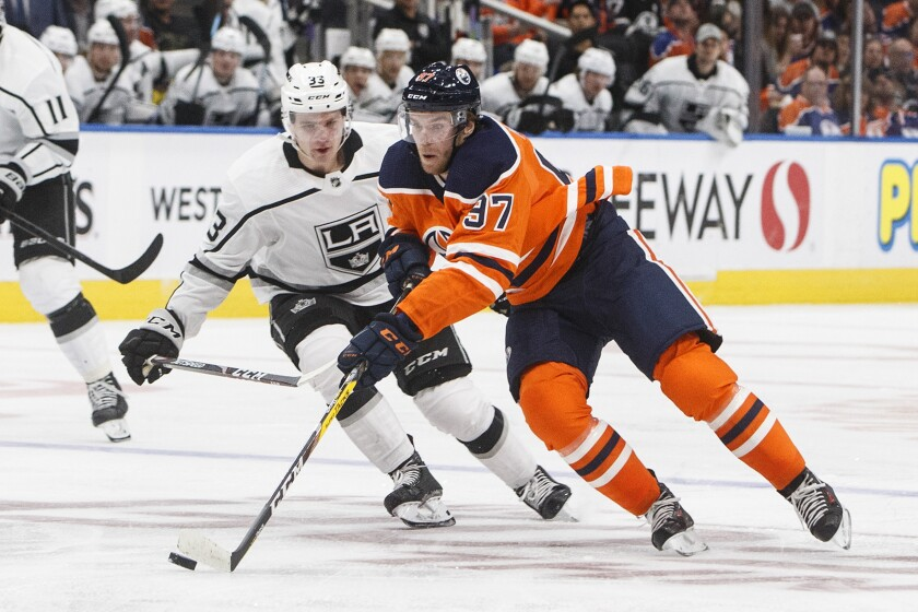 The Kings' Tobias Bjornfot chases the Oilers' Connor McDavid on Saturday night in Edmonton, Canada.