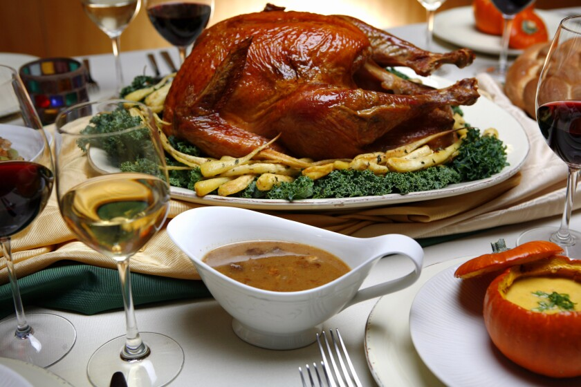 A Thanksgiving feast of salt–rubbed, roasted turkey with roasted parsnips, pan sauce and spiced pumpkin soup with maple syrup in roasted pumpkins.
