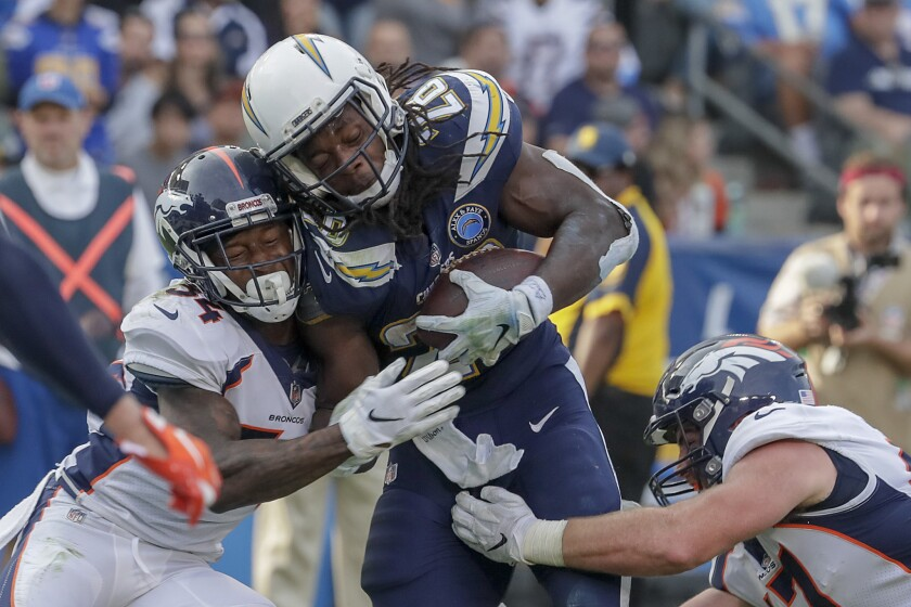 Chargers running back Melvin Gordon III is stopped short of the goal line by Denver Broncos safety Will Parks and linebacker Josie Jewell last November.