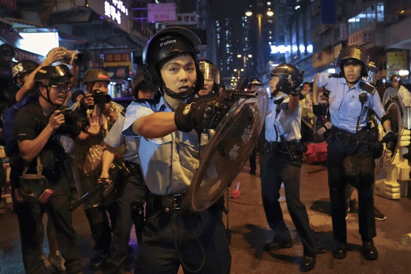 A policeman points a weapon during a protest in Hong Kong on Aug. 25, 2019.