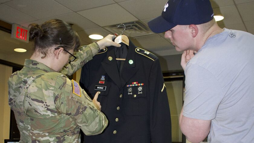 Army Staff Sgt. Cathrine Schmid examines a junior soldier's dress uniform, making sure the name tag