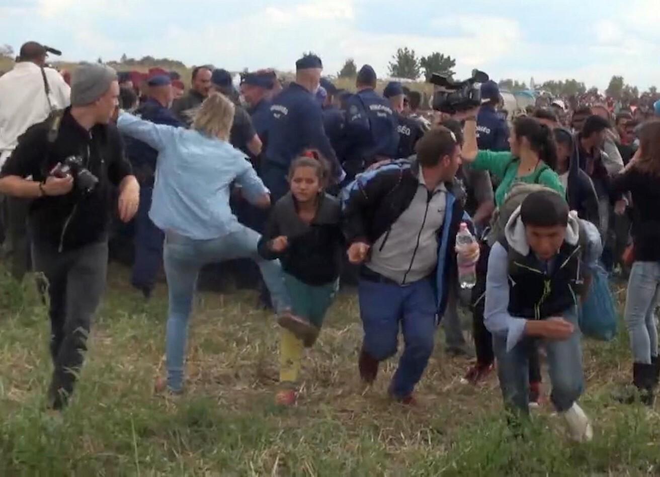 ARCHIVO - En esta foto del 8 de septiembre del 2015 tomada de televisión, una camarógrafa húngara, al centro, patea a una niña migrante que acaba de cruzar la frontera desde Serbia cerca de Roszke, Hungría. Petra Laszlo fue acusada formalmente de alterar la paz, informó la fiscalía de Hungría. (Index.Hu. via AP)