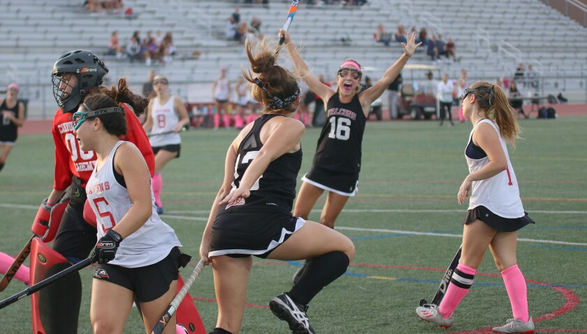 Stella Mikolajewski (#16) and Hailey Dewey (foreground) celebrate the game's first goal.