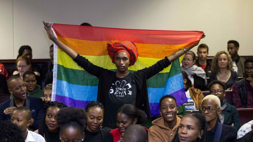 An activist holds up a flag in the courtroom to celebrate the Botswana High Court's rejection of sections of the penal code punishing same-sex relations. The court ruled in Gaborone on Tuesday.