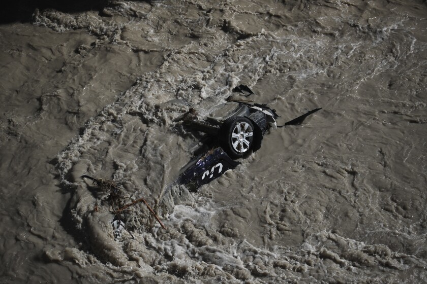A car was swept away during floods in the Roya river of Breil-sur-Roya, near the border with Italy, Monday, Oct.5, 2020. Flooding has devastated mountainous areas in France's southeastern region of Alpes-Maritimes and Italy's northwestern regions of Liguria and Piedmont, after a storm swept through the two countries on Friday and Saturday. (AP Photo/Daniel Cole)