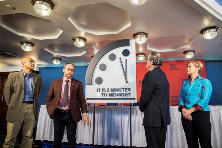 """(i-d) Sivan Kartha, científico del Instituto Medioambiental de Estocolmo, Lawrence Krauss, director del proyecto Origins de la Universidad de Arizona, Robert Rosner, profesor en la Universidad de Chicago, y Sharon Squassoni , profesora en la Universidad de Washington, tras el ajuste en 30 segundos del """"Reloj del Juicio Final"""" (Doomsday Clock) hasta colocar la manecilla a las 23.58 horas, un gesto que muestra un aumento de la posibilidades de que la humanidad alcance su destrucción total. EFE/EPA"""