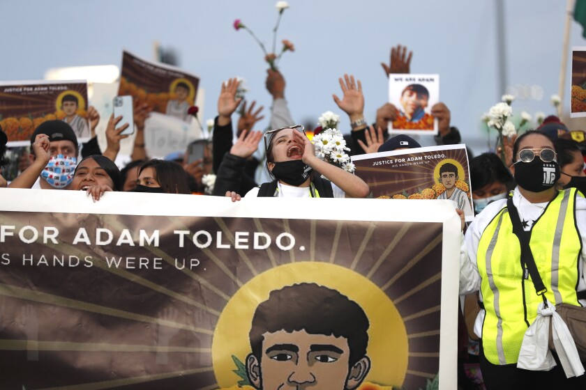 Protesters hold a banner with a drawing of Adam Toledo.