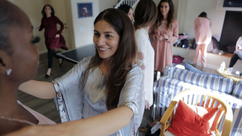 Artizara founder Sarah Ansari, center, adjust a model's clothing before a fashion show at her Encinitas home on Sunday. Her company specializes in selling modest, Islamic art-inspired fashion and lifestyle items.