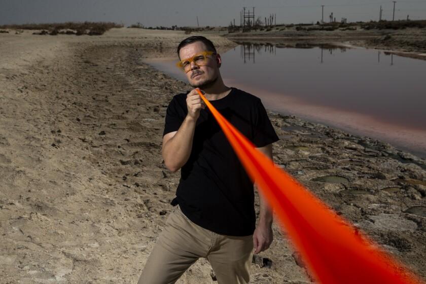 Environmental artist Cristopher Cichocki stands near the Anza Ditch in Salton City, Calif.