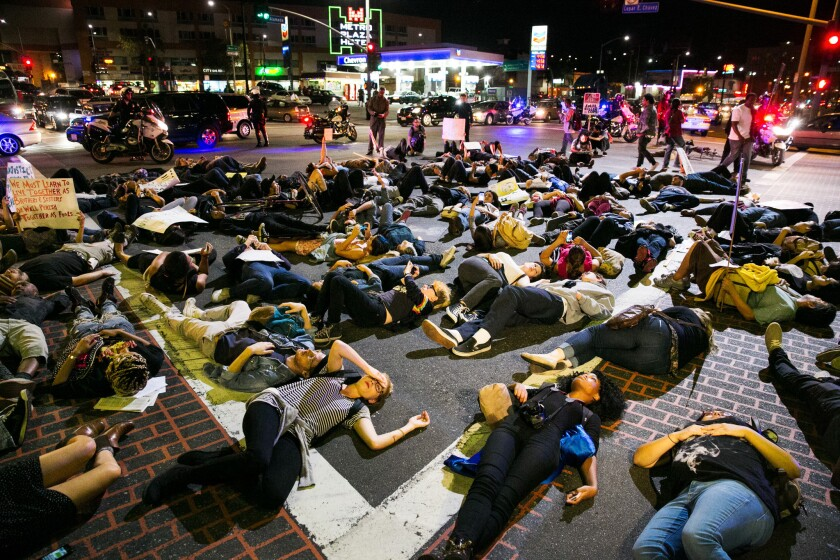 """Protesters stage a """"die-in"""" on a Los Angeles street Wednesday night to represent Michael Brown's body lying in the Ferguson, Mo., street where he was shot."""
