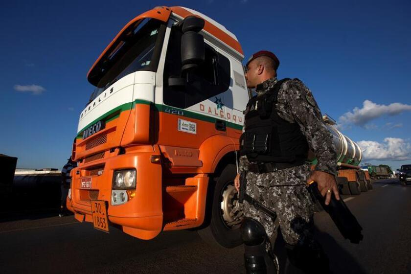 A member of the National Public Security Force (FNSP), made up of military police and civil police from different Brazilian states, asks a trucker taking part in a June 2018 road-blocking protest to move his vehicle. EPA-EFE/File