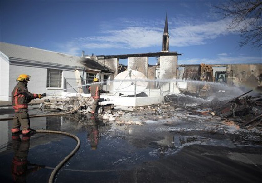 Firefighters spray water on the remains of the Church of Jesus Christ of Latter-day Saints in Logandale, Nev., Wednesday, Feb. 4, 2009. Clark County fire spokesman Scott Allison says there was no immediate indication of foul play in the 4 a.m. fire that engulfed the church. (AP Photo/Jae C. Hong)