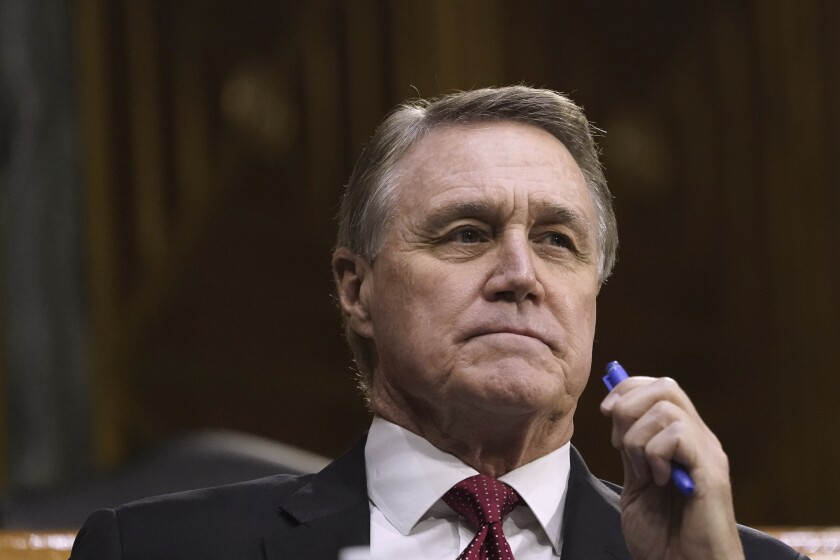 FILE - In this Sept. 24, 2020, file photo Sen. David Perdue, R-Ga., listens during the Senate's Committee on Banking, Housing, and Urban Affairs hearing on Capitol Hill in Washington. With in-person campaigning dampened by the coronavirus, advertising has taken on even greater importance in Perdue's race against Democrat Jon Ossoff. (Drew Angerer/Pool via AP, File)