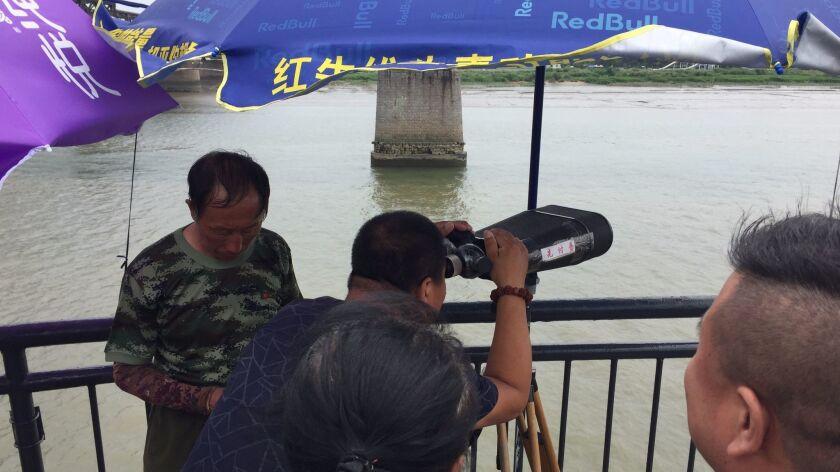 A Chinese tourist gazes through binoculars at North Korea, across the Yalu River.