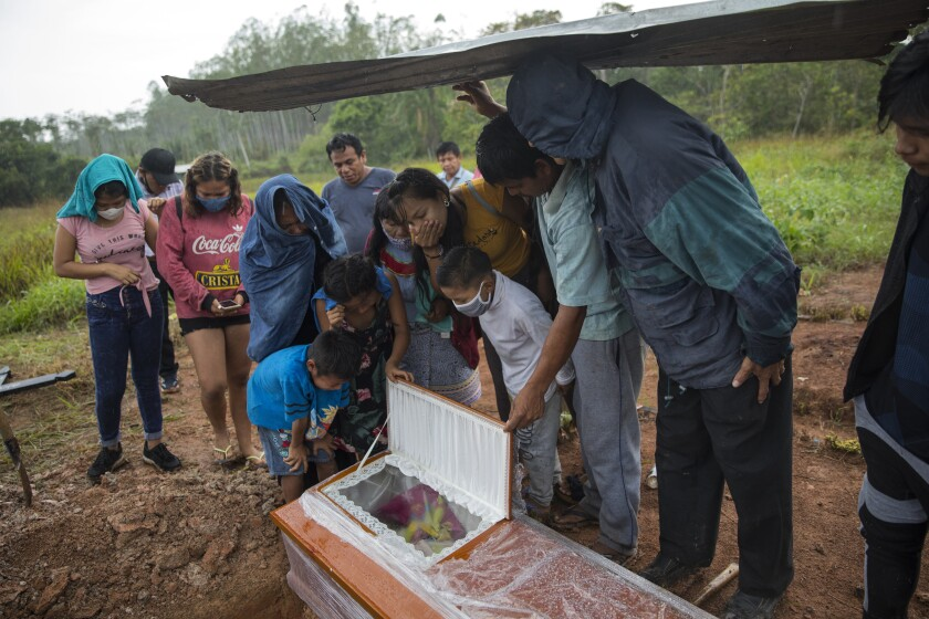 Family members look in the coffin that contains the remains of Manuela Chavez who died from symptoms related to the new coronavirus at the age of 88, during a burial service in the Shipibo Indigenous community of Pucallpa, in Peru's Ucayali region, Monday, Aug. 31, 2020. The Shipibo have tried to prevent COVID-19's entrance by blocking off roads and isolating themselves. (AP Photo/Rodrigo Abd)