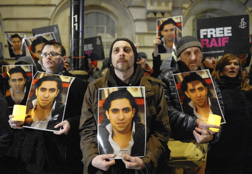 Protesters at the Saudi Embassy in London hold images of Saudi blogger Raif Badawi, who was flogged and faces 950 more lashes and 10 years in prison over posts the Saudi courts deemed offensive.