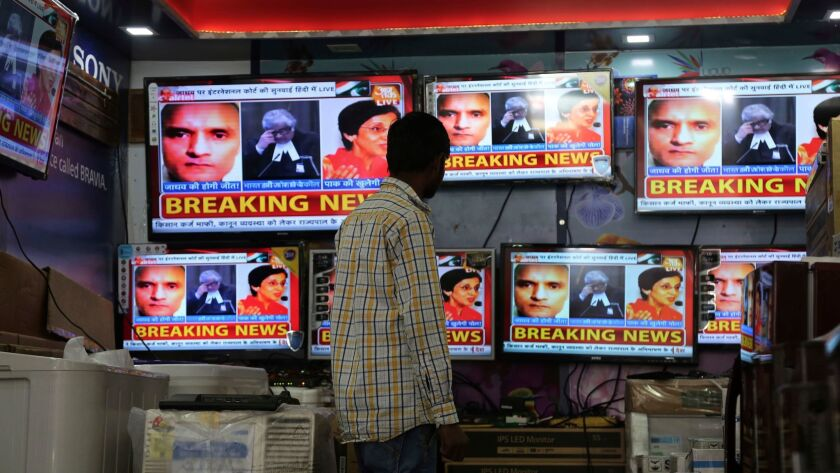An Indian boy watches as television channels show news about International Court of Justice hearing