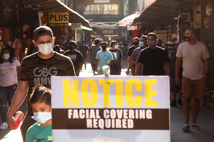 A sign at outdoor shopping center says Notice: Facial covering required