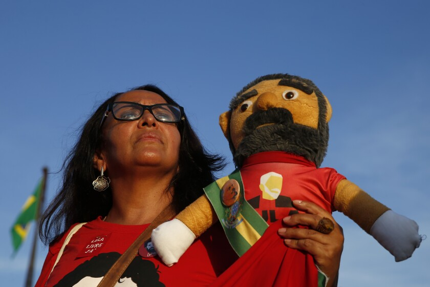A supporter of Luiz Inácio Lula da Silva holds a doll depicting the former Brazilian president outside Brazil's Supreme Court in Brasilia on Thursday.