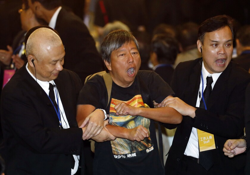 Pro-democracy lawmaker Lee Cheuk-yan, center, is taken away by security guards after a protest against Li Fei, deputy secretary general of China's National People's Congress standing committee, in Hong Kong on Monday.