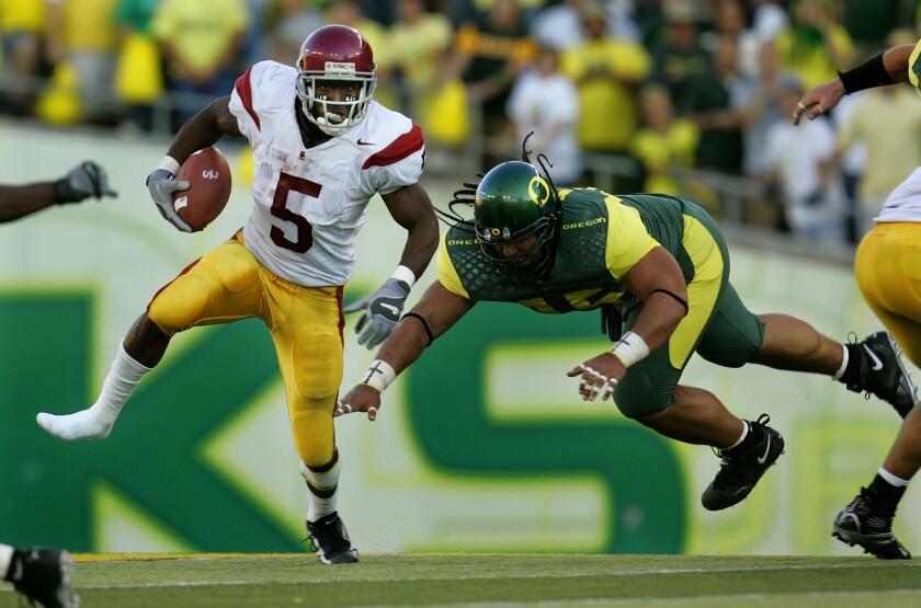 USC running back Reggie Bush eludes Oregon's Matt Toeaina during a game in September 2005.