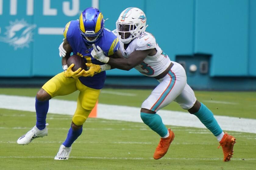 Miami Dolphins cornerback Noah Igbinoghene tackles Rams wide receiver Robert Woods.