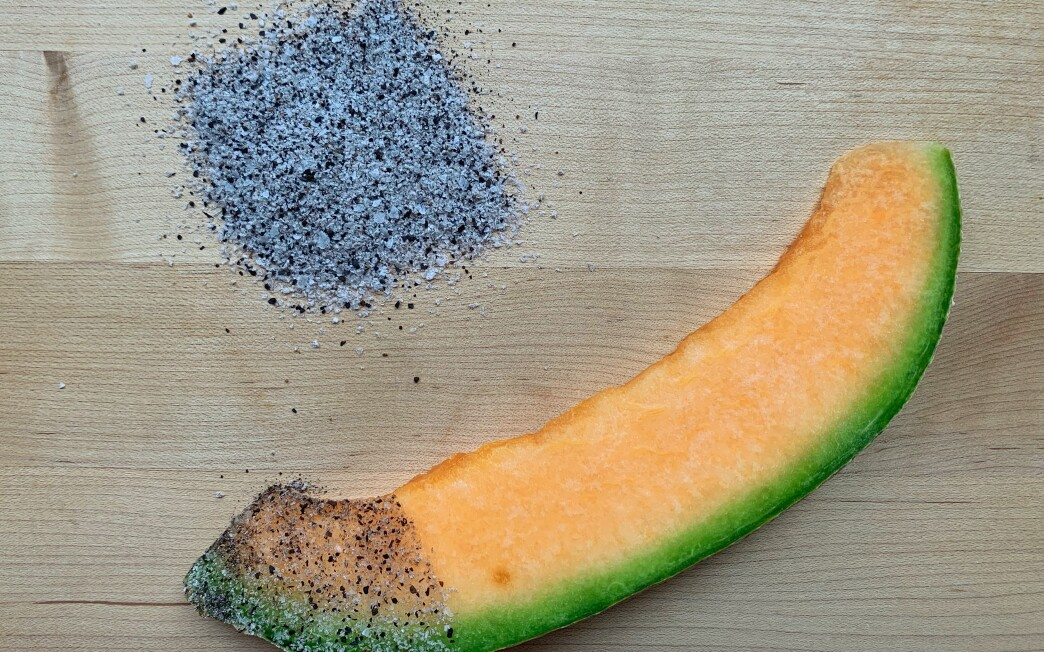 A slice of canteloupe dipped in sour black lime powder