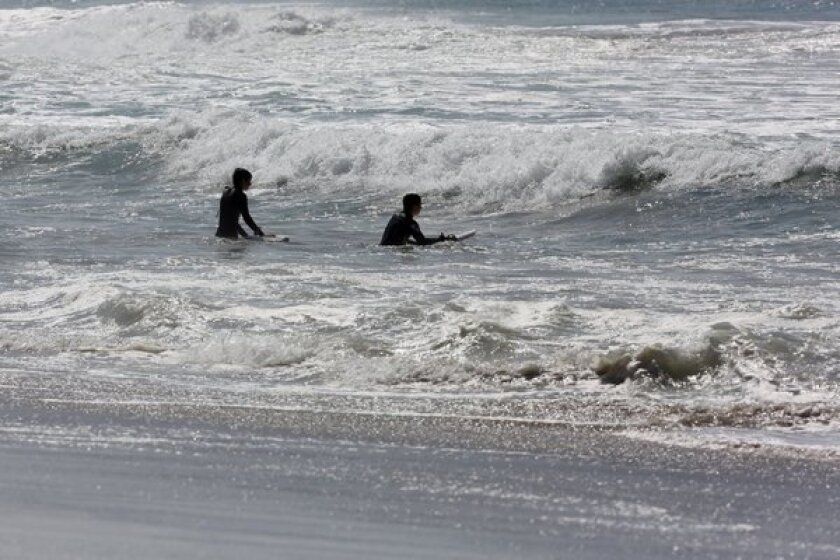 Strong rip currents are expected along south-facing beaches this weekend, including at Zuma Beach, where surfers enjoyed the waves in March.
