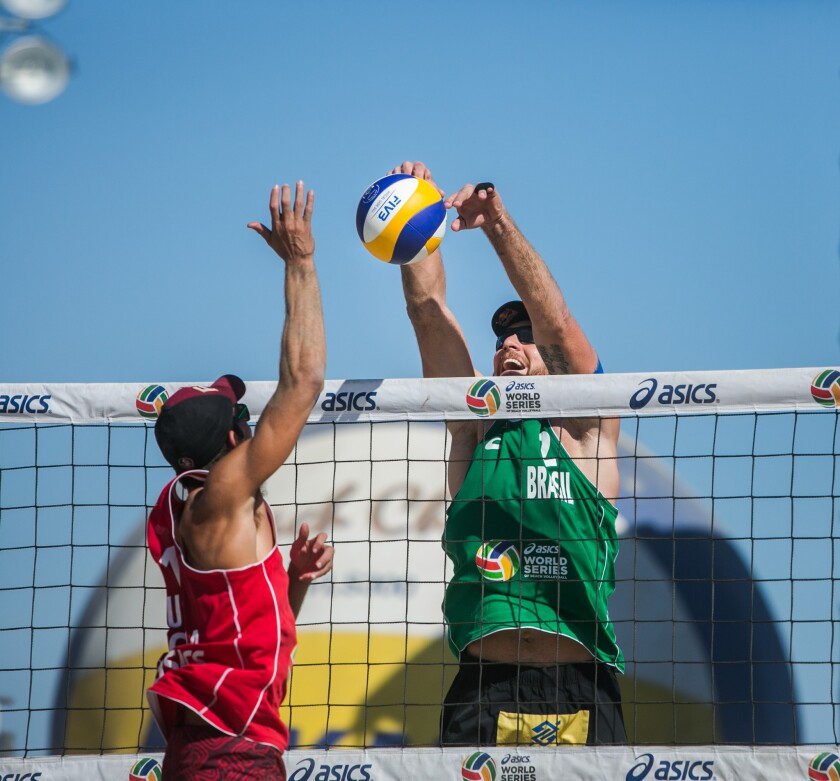 Alison Cerutti blocks a shot by Nick Lucena during the championship match of the World Series of Beach Volleyball.