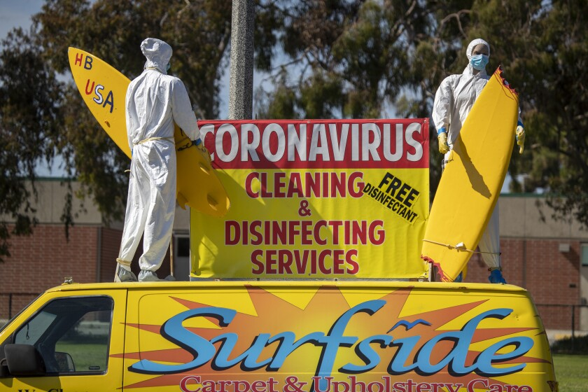 Surfer mannequins dressed in protective gear advertise coronavirus cleaning and disinfecting services atop a van parked by Surfside Carpet & Upholstery in Huntington Beach on Monday.