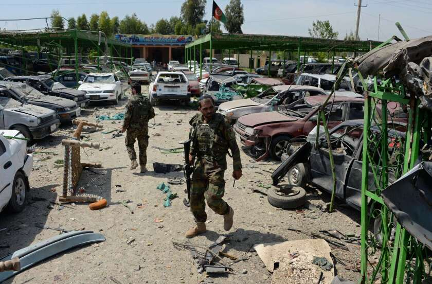 Afghan security personnel walk through the site of a suicide car bomb attack targeting a NATO convoy near the airport in Jalalabad on Friday.