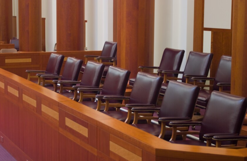 Empty jury box in a large, modern courtroom.