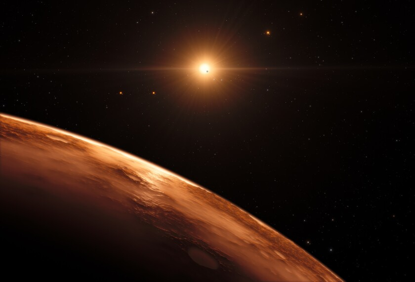 An artist's impression shows the view just above the surface of one of the planets in the TRAPPIST-1 system. At least seven planets orbit this ultra-cool dwarf star 40 lightyears from Earth and they are all roughly the same size as the Earth.