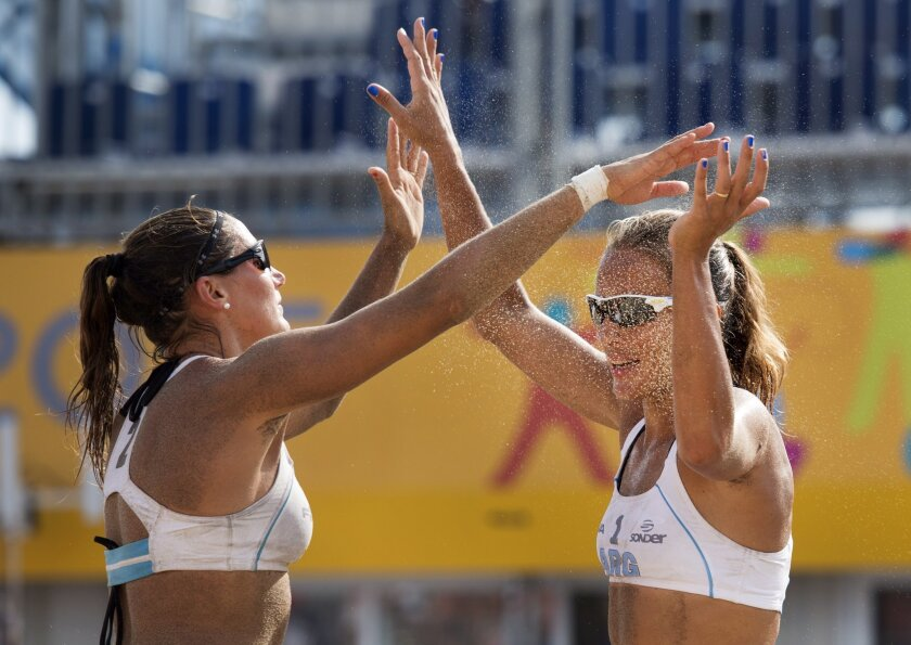 Ana Gallay, right, and Georgina Klug, of Argentina, celebrate a point during a women's beach volleyball quarterfinal action against the United States at the Pan Am Games in Toronto, Saturday, July 18, 2015. Argentina defeated the U.S. in straight sets. (Darren Calabrese/The Canadian Press via AP)