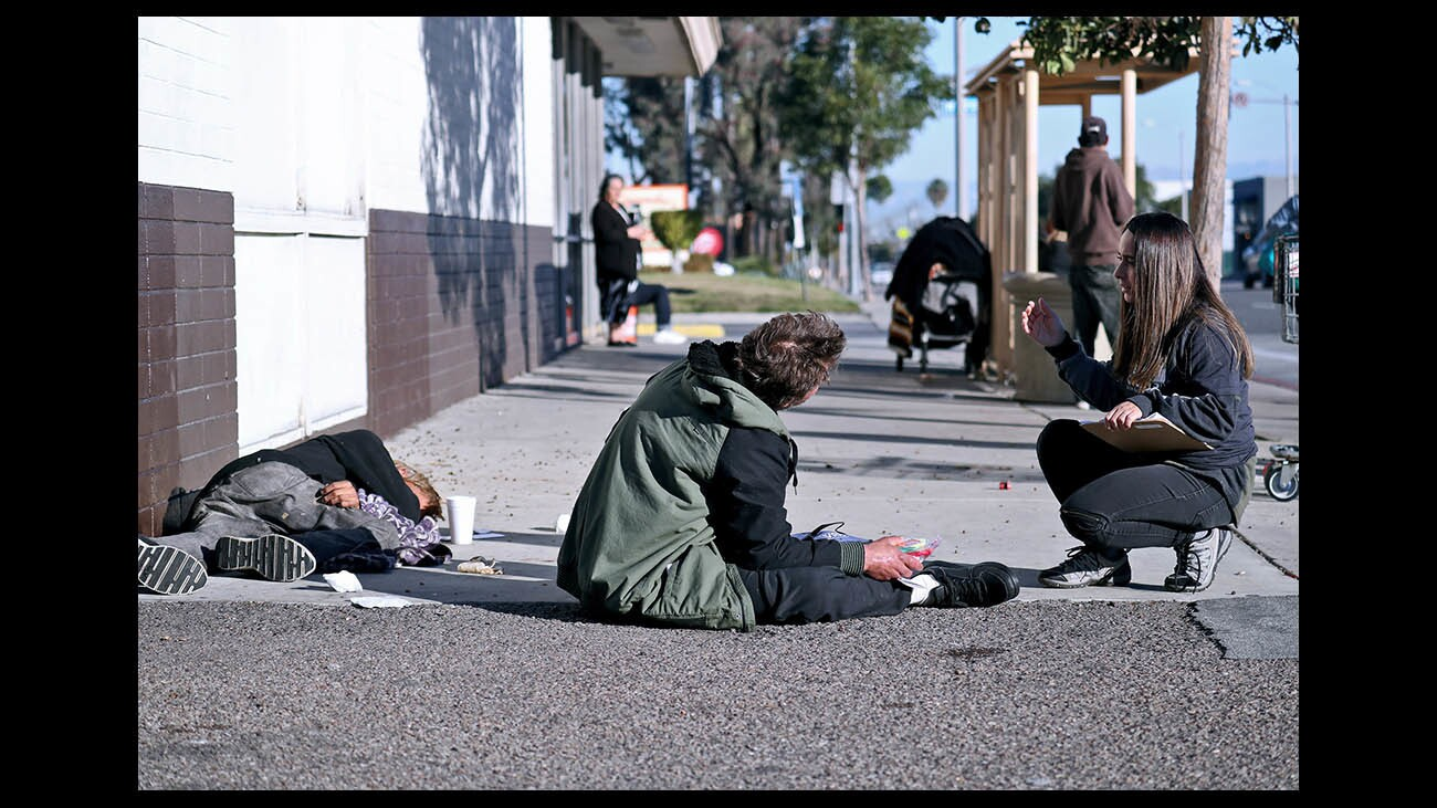 City Net case manager Jennifer Munoz speaks with a homeless man in Costa Mesa.