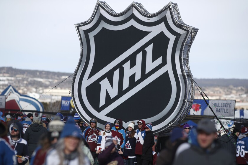 In this Feb. 15, 2020, photo, fans pose below the NHL logo outside Falcon Stadium before an outdoor game between the Kings and Colorado Avalanche in Colorado Springs, Colo.