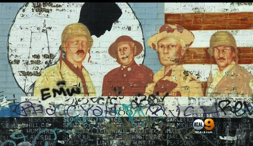 This Friday, May 27, 2016 image from video provided by KCBS-TV/KCAL-TV shows graffiti on a Vietnam War memorial in the Venice area of Los Angeles. The homespun memorial painted on a block-long wall on Pacific Avenue lists the names of American service members missing in action or unaccounted for in Southeast Asia, painted by a Vietnam veteran and dedicated in 1992. The wall has been tagged previously but the latest vandalism - within the past week - covers the bottom half of the memorial for much of its length. (KCBS-TV/KCAL-TV via AP) TV OUT; MANDATORY CREDIT