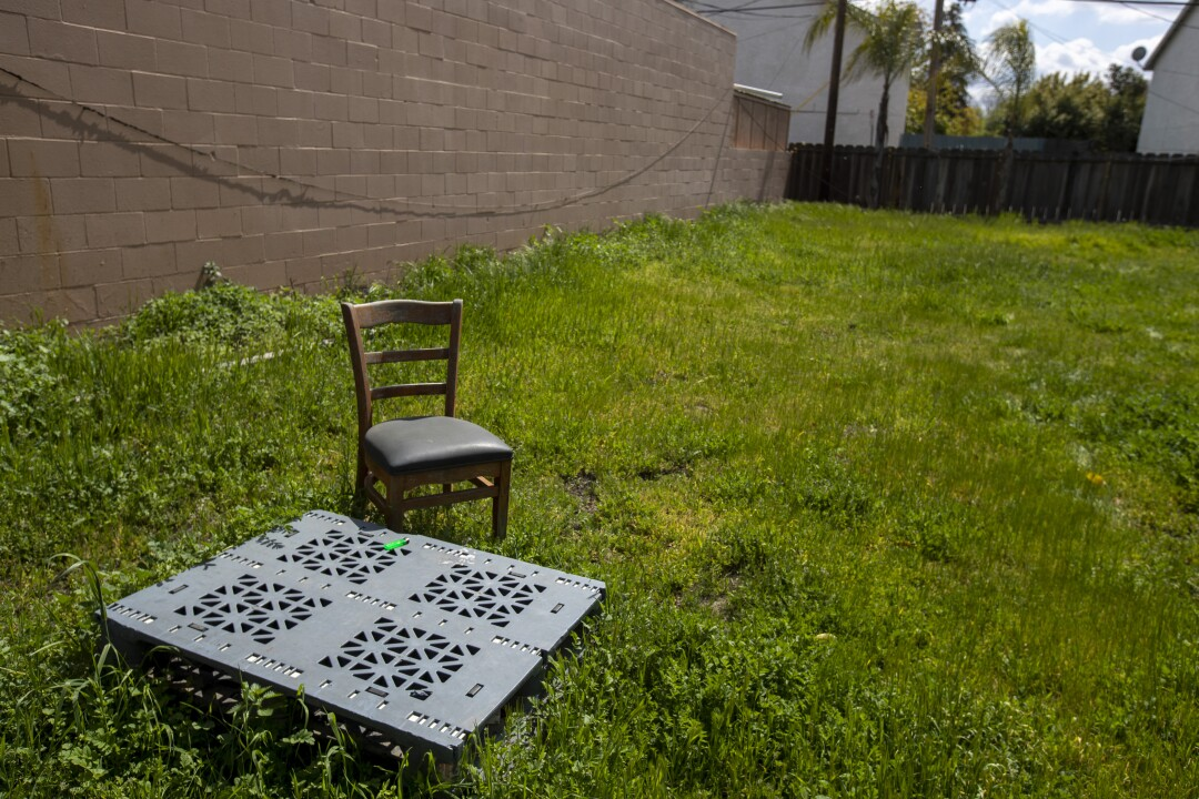 A grassy lot with a square, metal covering and a chair.