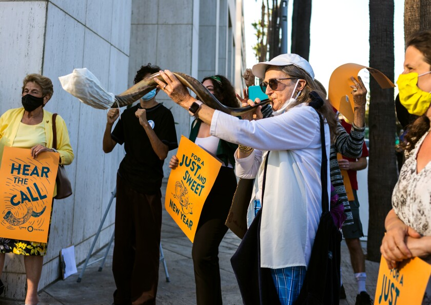 Climate protesters carry signs and blow a shofar