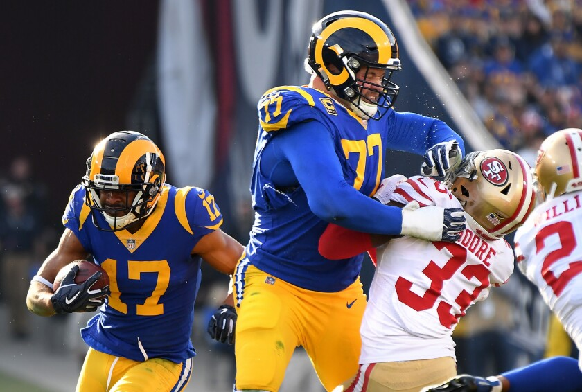 Rams tackle Andrew Whitworth (77) provides a block for receiver Robert Woods (17) during a game against the 49ers and Tarvarius Moore (33).