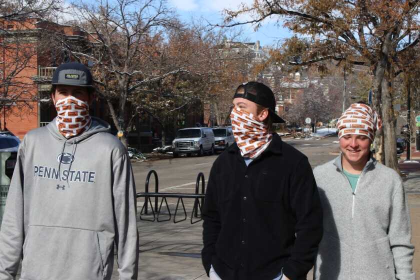 Two men wear masks and a third, smiling, wears his mask on his head in in Boulder, Colo.