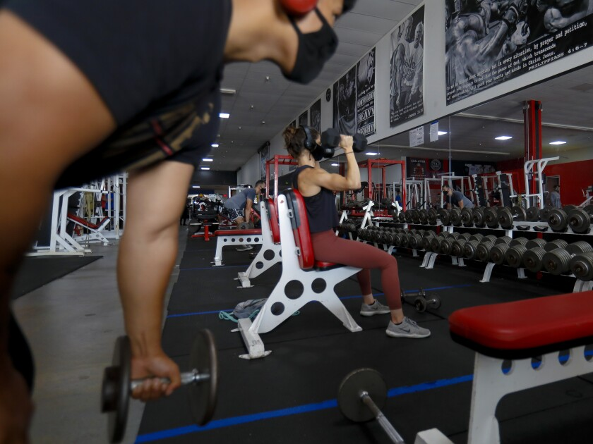Gym members Michael Perez and April Glassell run through several sets during their workout at Metroflex Gym in Oceanside.