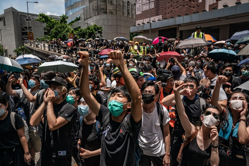 Pro-democracy protesters in Hong Kong shout slogans outside police headquarters in June 2019.