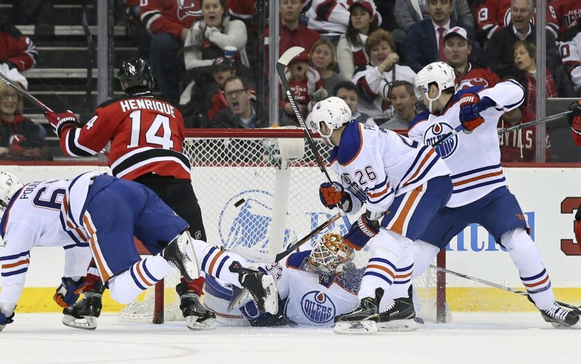 Edmonton Oilers goalie Cam Talbot (33) falls to the ice as he can't stop a shot by New Jersey Devils center Adam Henrique (14) during the first period of an NHL hockey game Tuesday, Feb. 9, 2016, in Newark, N.J.  (AP Photo/Mel Evans)