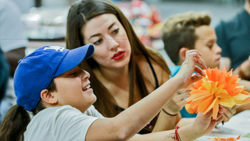 Shantal Verduzco, right, helps Isabel Fort, 10, make art during a youth workshop held at Self Help Graphics in Boyle Heights.