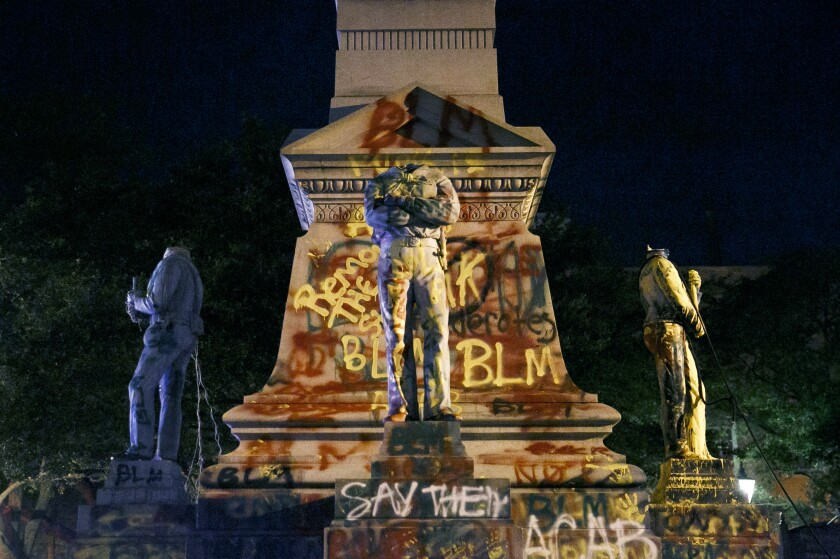 The statues on the Confederate monument are covered in graffiti and beheaded after a protest in Portsmouth, Va., Wednesday, June 10, 2020. Protesters beheaded and then pulled down four statues that were part of a Confederate monument. The crowd was frustrated by the Portsmouth City Council's decision to put off moving the monument. (Kristen Zeis/The Virginian-Pilot via AP)