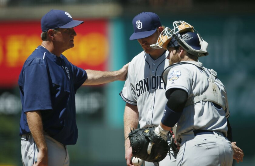 San Diego Padres pitching coach Darren Balsley, left, confers with starting pitcher Erik Johnson as catcher Derek Norris looks on as Johnson struggles against the Colorado Rockies in the first inning of a baseball game Saturday, June 11, 2016, in Denver. (AP Photo/David Zalubowski)