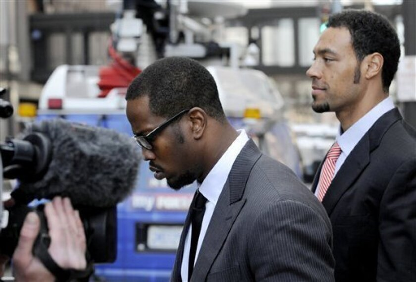 Von Miller, left, a Texas A&M football player who plans to enter the NFL draft, and San Diego Chargers' Vincent Jackson head toward a bus outside the federal courthouse after a hearing Wednesday, April 6, 2011, in St Paul, Minn. A group of players is asking a judge to issue a preliminary injunction